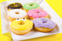 Strawberry, chocklate and other donuts in paper box on yellow background Stock Images
