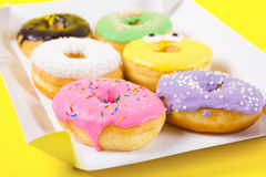 Strawberry, chocklate and other donuts in paper box on yellow background Stock Photography