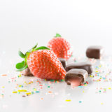 Strawberry and Chocolate. Strawberries, cream filled chocolates and colored candy confetti on white background Stock Photos