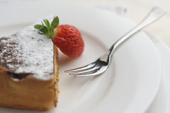 Strawberry and Chocolate dessert with fork; macro wide view. Closely cropped macro shot from above of a Chocolate cheesecake dessert slice with a cut strawberry Royalty Free Stock Photos