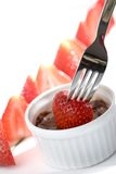 Strawberry in chocolate fondue. Focus on fork, closeup Royalty Free Stock Photo