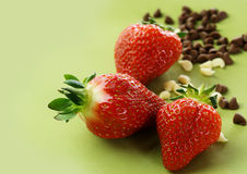 Strawberry and chocolate sprinkle. Strawberry and chocolate sparkle on green clean background Stock Photos