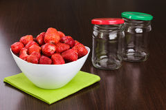 Strawberry cleared in a white bowl and empty jars Stock Photos