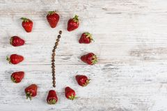Strawberry clock with arrows of coffee beans, showing twelve hours thirty minutes on a wooden antique table in the kitchen. Flat Lay. Background for a postcard stock photography