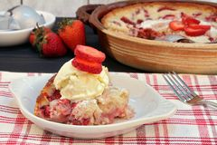 Strawberry Cobbler with vanilla ice cream. A serving of fresh strawberry cobbler with a scoop of vanilla ice cream and garnished with strawberry slices royalty free stock images