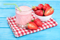 Strawberry cocktail. Delicious strawberry cocktail with milk and fresh berries in a bowl, on a towel and a blue table royalty free stock photography