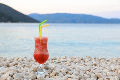 Strawberry cocktail. Evening relaxation with a glass of strawberry cocktail during the summer holidays on the Antisamos beach,. Kefalonia island, Greece royalty free stock image