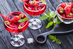 Strawberry cocktail with ice and fresh mint on a black wooden table Royalty Free Stock Photo