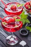 Strawberry cocktail with ice and fresh mint on a black wooden table Stock Image