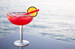 Strawberry cocktail. Romantic strawberry margarita cocktail served against an ocean background Royalty Free Stock Images