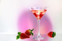 Strawberry cocktail. Strawberries and drink on purple pink background Stock Images