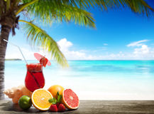 Strawberry cocktail and tropical fruit. On the beach stock image