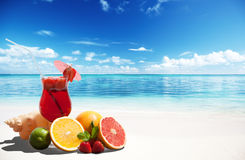 Strawberry cocktail and tropical fruit. On the beach Royalty Free Stock Images