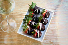 A strawberry compliment. Shallow DOF. A plate of strawberries in chocolate on a glass surface with a glass of wine Stock Image