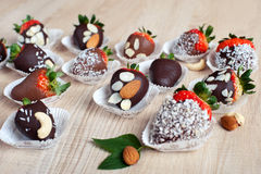 Strawberry covered with milk and dark chocolate and coconut flak. Variety of strawberries covered with milk and dark chocolate and coconut flakes and almond nuts Stock Images
