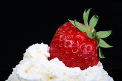 Strawberry Cream. Fresh strawberry placed on whipped cream  with black background Stock Photo