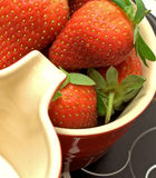 Strawberry cream. Strawberries and cream macro against black background placemats Royalty Free Stock Image