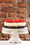 Strawberry cream cake on brick wall background Stock Photo