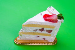 Strawberry cream cake in green background Royalty Free Stock Image