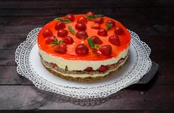 Strawberry cream cheese cake on mahogany wood background