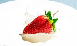 Strawberry on cream. Strawberry splashing over cream on plate Royalty Free Stock Images