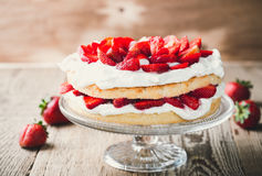 Strawberry and cream sponge cake. On glass stand. Homemade summer dessert on wooden rustic table Stock Photos