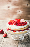 Strawberry and cream sponge cake. On glass stand. Homemade summer dessert on wooden rustic table Royalty Free Stock Images