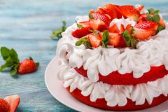 Strawberry and cream sponge cake. Homemade summer dessert on wooden table. Strawberry and cream sponge cake. Homemade summer dessert on wooden blue table royalty free stock images