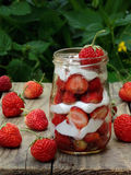 Strawberry with cream. Strawberries with cream in a jar on a wooden background royalty free stock photos