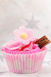 Strawberry cup cake. Home made pink strawberry cup cake with a chocolate flake and edible flower decoration Royalty Free Stock Image