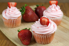 Strawberry Cupcaakes. Strawberry cupcakes with fresh strawberries  on a table top Royalty Free Stock Image