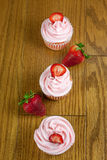 Strawberry Cupcaakes. Strawberry cupcakes with fresh strawberries  on a table top Stock Photography