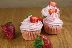 Strawberry Cupcaakes. Strawberry cupcakes with fresh strawberries  on a table top Royalty Free Stock Images