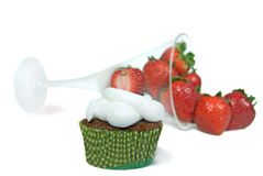 Strawberry on cupcake. Fresh strawberries spilling out of glass with chocolate cupcake Stock Images