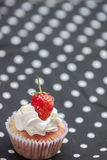 Strawberry cupcake. With Strawberry on a polka dot apron stock image