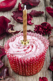 Strawberry cupcake with a golden candle Royalty Free Stock Images