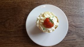 Strawberry cupcake on white plate. Strawberry cupcake on the wooden table. Top view Royalty Free Stock Photo