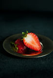 Strawberry cut in half on small metal plate Stock Image