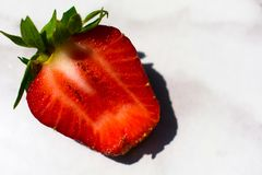 Strawberry cut in half on a white marble table. royalty free stock photography