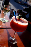 Strawberry daiquiri. Frozen strawberry daiquiri on a table with a glass of white wine Royalty Free Stock Photography