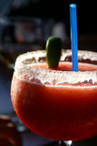 Strawberry daiquiri. Frozen strawberry daiquiri with a blue straw and green lemon Royalty Free Stock Images