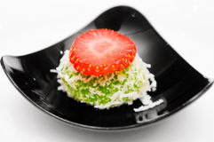Strawberry Dessert. Green dessert with coconut and strawberry topping. White background Royalty Free Stock Photography