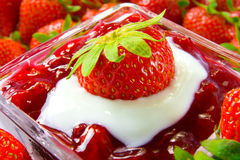 Strawberry dessert. A closeup of a dessert with strawberries and red fruit compote topped with white cream and a strawberry with green leaves stock image