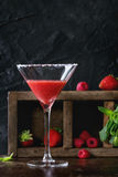 Strawberry dessert cocktail. Sugared glass with strawberry dessert cocktail, served on dark background with Strawberries, raspberries and mint behind. With copy stock image