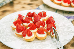 Strawberry dessert with cream on a white plate Stock Photos