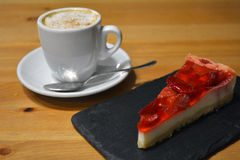 Strawberry dessert with cup of cappuccino on the wooden table Royalty Free Stock Images