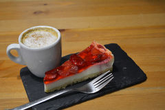 Strawberry dessert with cup of cappuccino on the wooden table Stock Photography