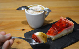 Strawberry dessert with cup of cappuccino on the wooden table Royalty Free Stock Image