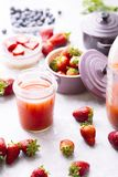 Strawberry detox juice. Frontal view of strawberry detox juice in w berries inside ceramic colored cocotte, blueberries, strawberries, raspberries, flat lay Stock Photo