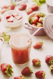 Strawberry detox juice. Frontal view of strawberry detox juice in w berries inside ceramic colored cocotte, blueberries, strawberries, raspberries, flat lay Stock Images